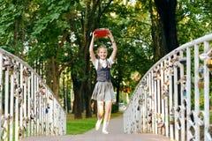 Studentenschoolmeisje gelukkig met vlechten in eenvormig met boeken in handen boven hoofdlooppas over brid royalty-vrije stock fotografie
