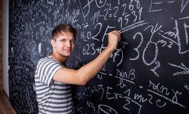 Studentenschreiben auf großer Tafel mit mathematischen Symbolen Stockbild