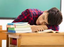 Studentenslaap op het bureau in klaslokaal stock afbeeldingen