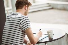 Studentenzitting met een hete drank en het schrijven op blocnote Stock Fotografie