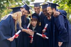 Studenter eller ungkarlar med diplom och smartphonen Arkivfoton