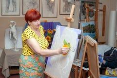 Studenter för vuxna kvinnor sitter på staffli som studerar målning arkivfoton