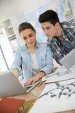 Studenter i arkitektur som arbetar på projekt genom att använda minnestavlan arkivfoto