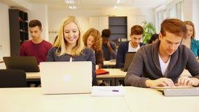 Studenter i klassrum genom att använda datoren lager videofilmer