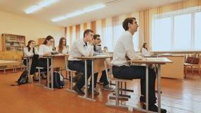 Studenter i klassrumet är på deras skrivbord Rysk skola arkivfilmer