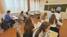 Studenter i klassrumet är på deras skrivbord Rysk skola lager videofilmer
