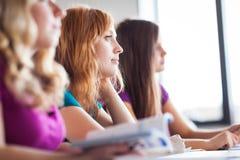 Studenter i klassrumet - ung nätt kvinnlig högskolestudent royaltyfri bild
