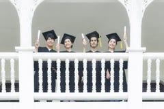 Studenter, i mening lyckliga med avläggande av examenkappor, står på corridoen arkivbild