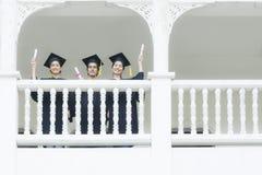 Studenter, i mening lyckliga med avläggande av examenkappor, står på corridoen arkivfoton