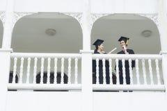 Studenter, i mening lyckliga med avläggande av examenkappor, står på corridoen royaltyfri bild