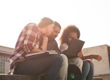 Studenter med bärbara datorn i universitetsområde Arkivbild