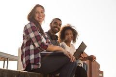 Studenter med bärbara datorn i universitetsområde royaltyfri bild
