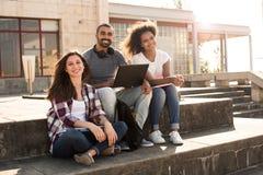 Studenter med bärbara datorn i universitetsområde fotografering för bildbyråer