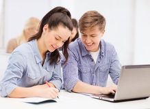 Studenter med bärbara datorn och anteckningsböcker på skolan Arkivfoton
