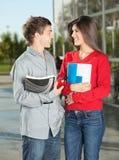Studenter med böcker som ser på de Fotografering för Bildbyråer