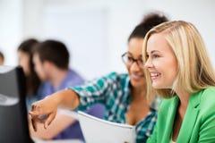 Studenter med datoren som studerar på skolan Arkivfoton