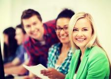 Studenter med datoren som studerar på skolan Royaltyfri Foto