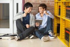Studenter med den Digital minnestavlan som griper hårt om näven medan Arkivfoton