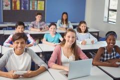 Studenter med den digitala minnestavlan och bärbara datorn i klassrum fotografering för bildbyråer