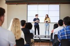 Studenter med Digital minnestavlor som ger presentation till högstadiumgrupp i Front Of Screen royaltyfria foton