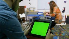 Studenter med en grön skärmminnestavlaPC som väntar på läraren i klassrum arkivfilmer