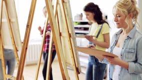 Studenter med staffli som målar på konstskolan stock video