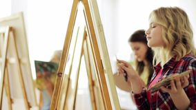 Studenter med staffli som målar på konstskolan arkivfilmer