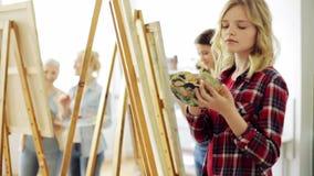 Studenter med staffli som målar på konstskolan lager videofilmer
