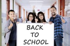 Studenter med tillbaka till skolatext ombord Royaltyfri Foto
