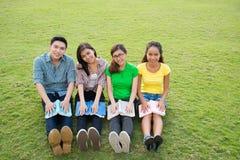 Studenter på gräsmatta Arkivbilder