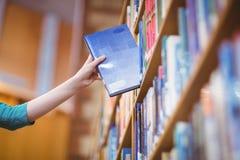 Studenter räcker med smartwatchplockningboken från bokhyllan arkivfoton