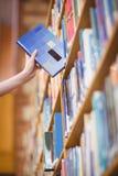 Studenter räcker med smartwatchplockningboken från bokhyllan royaltyfri foto
