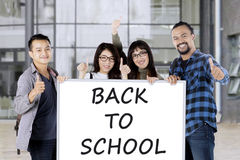 Studenter rymmer brädet med tillbaka till skolatext Royaltyfri Fotografi