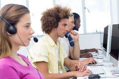 Studenter som använder hörlurar med mikrofon i datorgrupp Royaltyfri Fotografi