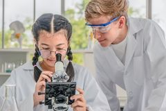 Studenter som använder mikroskopet i grupp för vetenskapslaboratorium arkivbild