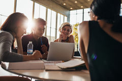 Studenter som använder bärbara datorn, medan sitta tillsammans i grupp Arkivfoto