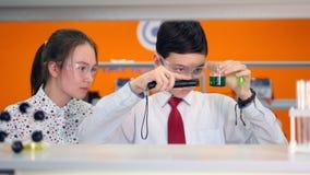 Studenter som arbetar på en kemi, projekterar tillsammans i kemiklassrum på skolan stock video