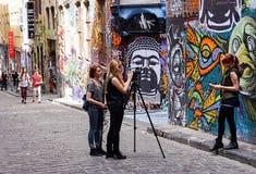 Studenter som framme filmar intervju av grafittikonst