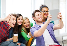 Studenter som gör bilden med minnestavlaPC på skolan Royaltyfri Bild