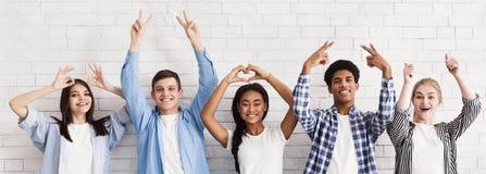 Studenter som gör en gest med händer över den vita väggen royaltyfri foto