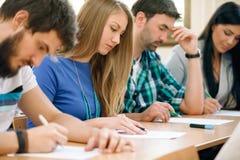 Studenter som har ett prov i ett klassrum Arkivbilder