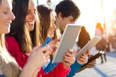 Studenter som har gyckel med smartphones och minnestavlor efter grupp Royaltyfria Bilder