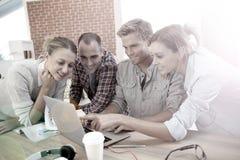 Studenter som har gyckel på en bärbar dator Arkivfoto