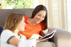 Studenter som hemma studerar på en soffa arkivfoton