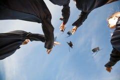 Studenter som kastar på mortelbräden i luft Fotografering för Bildbyråer