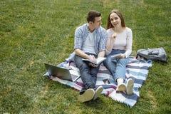 Studenter som ler, medan läsa och genom att använda bärbara datorn på grönt gräs i parkera lycklig utbildning royaltyfria foton