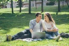 Studenter som ler, medan läsa och genom att använda bärbara datorn på grönt gräs i parkera lycklig utbildning royaltyfria bilder