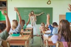 Studenter som lyfter händer i en matematikkurs Royaltyfri Foto
