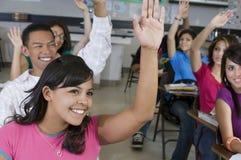 Studenter som lyfter händer i klassrum Royaltyfri Foto