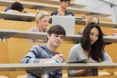 Studenter som lyssnar och tar anmärkningar i en föreläsning Royaltyfri Bild